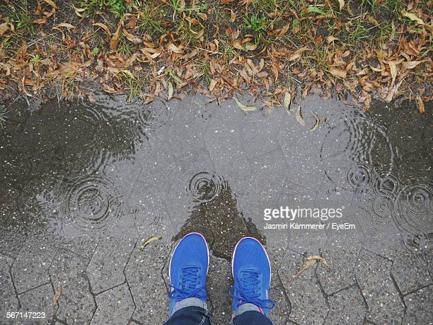 Low Section Of Man Standing On Wet Street During Rainy Season