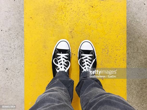 low section of man standing on yellow concrete footpath - pedestrian walkway stock pictures, royalty-free photos & images