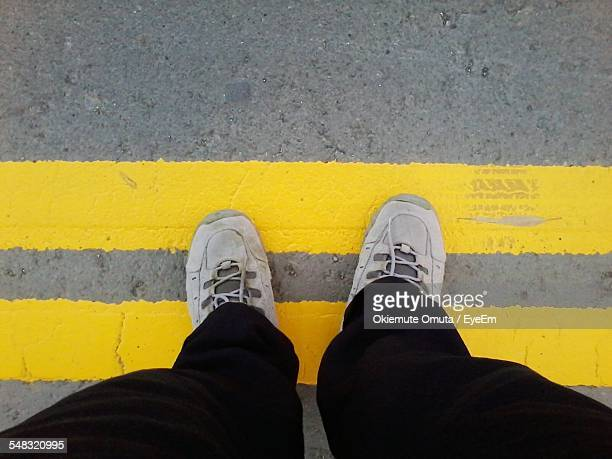 Low Section Of Man Standing On Yellow Lines