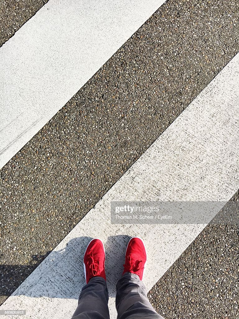 Low Section Of Man Standing On Zebra Crossing : Stock Photo