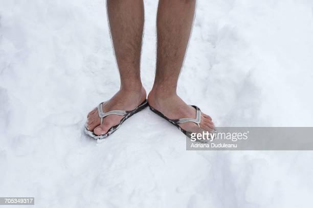 low section of man standing outdoors - ciabatta infradito foto e immagini stock