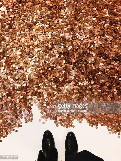 Low Section Of Man Standing With Coins On White Background
