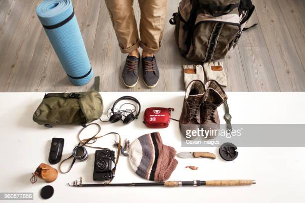 Low section of man standing with hiking and fishing gear arranged on table at home
