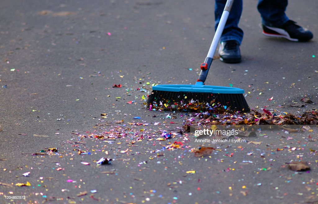 Low Section Of Man Sweeping Street : Stock Photo