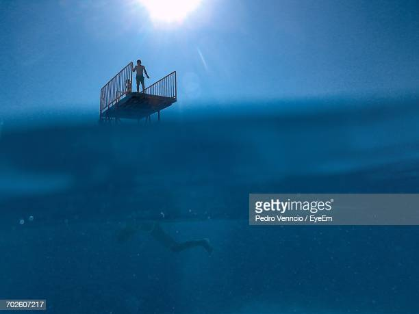 Low Section Of Man Swimming In Pool Against People On Diving Platform