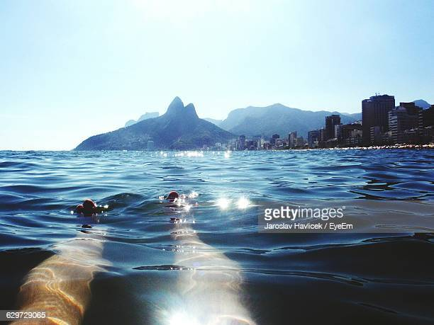 Low Section Of Man Swimming In Sea At Ipanema Beach