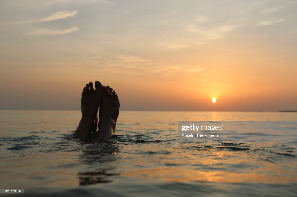 Low Section Of Man Swimming In Sea During Sunset : Stock-Foto