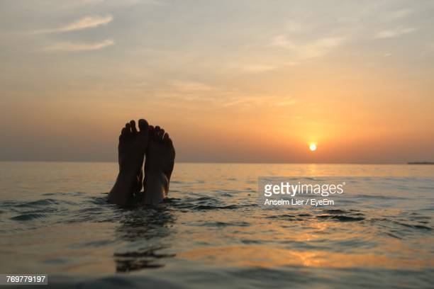 Low Section Of Man Swimming In Sea During Sunset