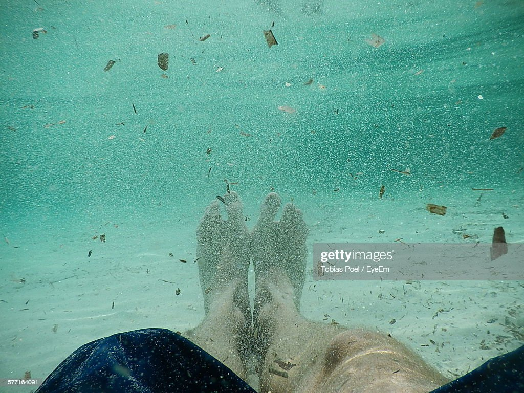 Low Section Of Man Swimming In Sea : Stock Photo