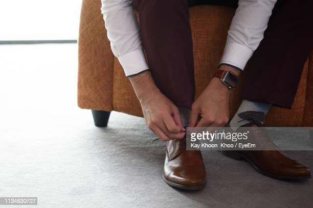 low section of man tying shoe laces while sitting at home - tying shoelace stock pictures, royalty-free photos & images