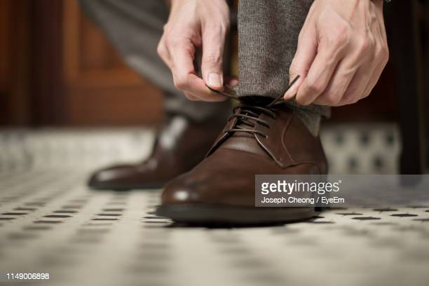 low section of man tying shoelace at home - tie stock pictures, royalty-free photos & images