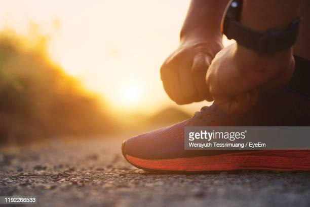 low section of man tying shoelace on land during sunset - tying shoelace stock pictures, royalty-free photos & images