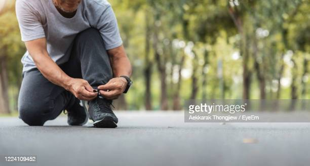 low section of man tying shoelace on road - tying shoelace stock pictures, royalty-free photos & images