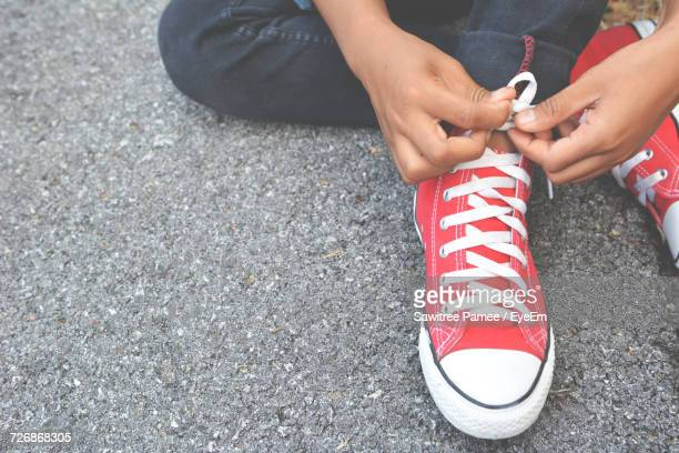 Low Section Of Man Tying Shoelace On Road