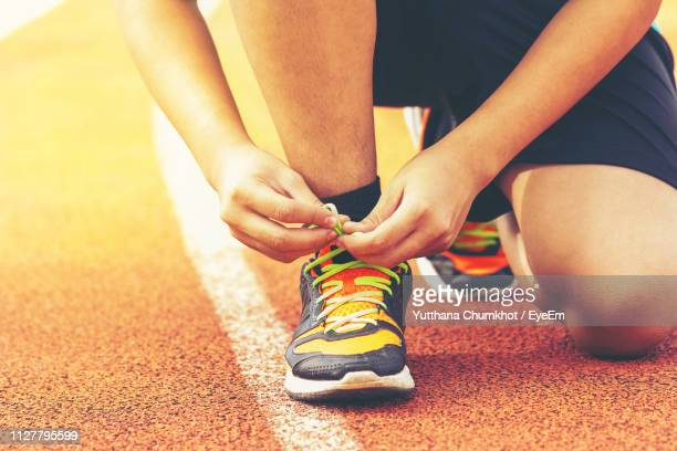 low section of man tying shoelace on running track - sports footwear stock pictures, royalty-free photos & images