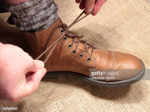 low section of man tying shoelace - tying shoelace stock pictures, royalty-free photos & images