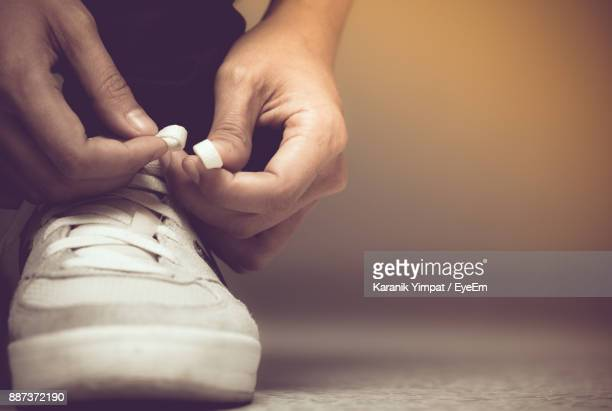 low section of man tying shoelace - tie stock pictures, royalty-free photos & images
