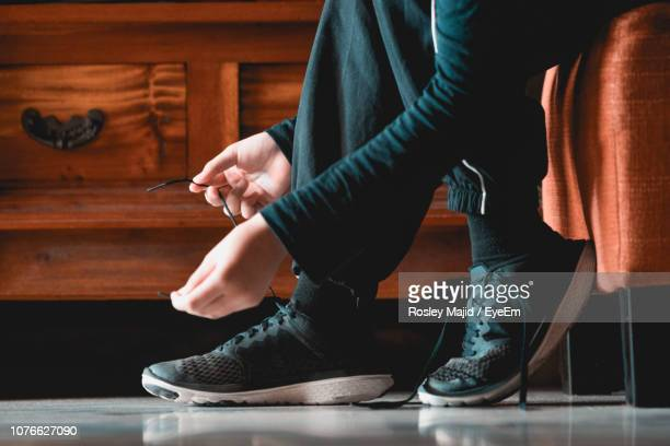 low section of man tying shoelace while sitting on chair at home - tied up stock pictures, royalty-free photos & images