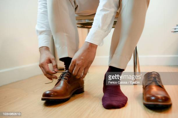 low section of man tying shoelaces on hardwood floor at home - brown shoe stock photos and pictures