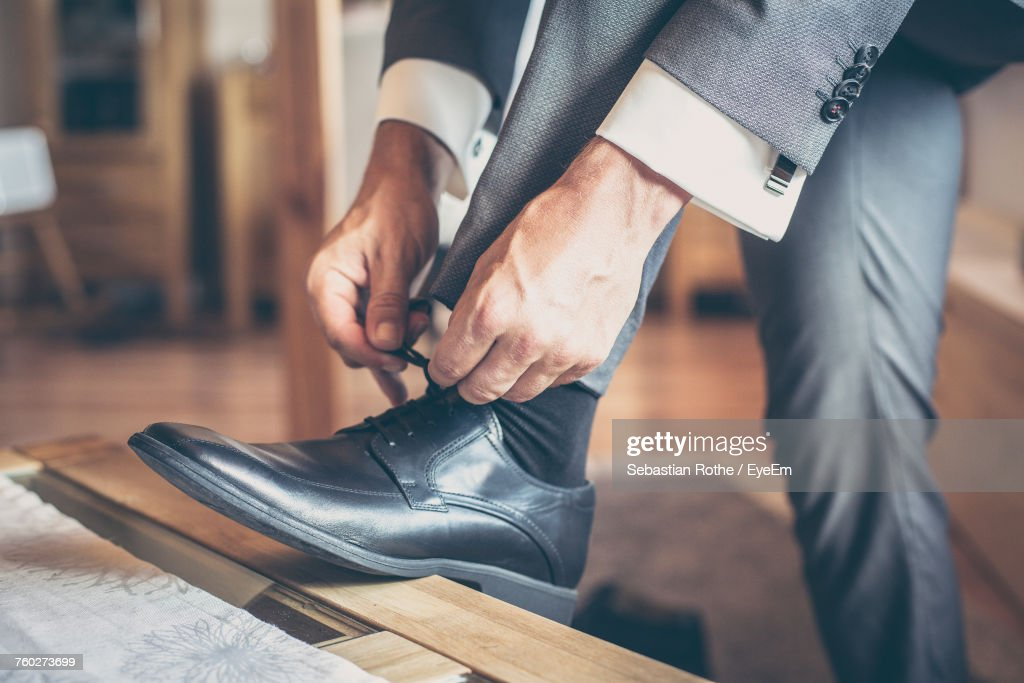 Low Section Of Man Tying Shoes : Stock Photo