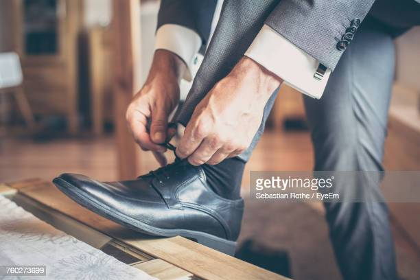 low section of man tying shoes - calzature di pelle foto e immagini stock