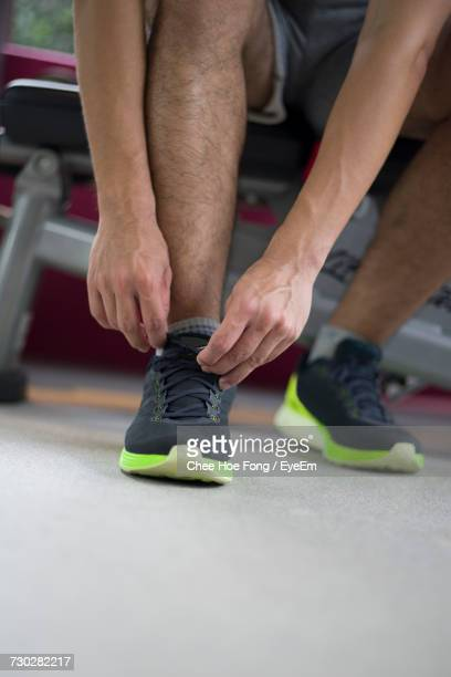 Low Section Of Man Tying Trainers