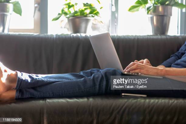 low section of man using laptop on sofa at home - paulien tabak 個照片及圖片檔