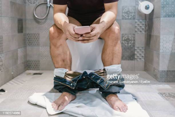 low section of man using mobile phone while sitting in bathroom - human toilet stock-fotos und bilder