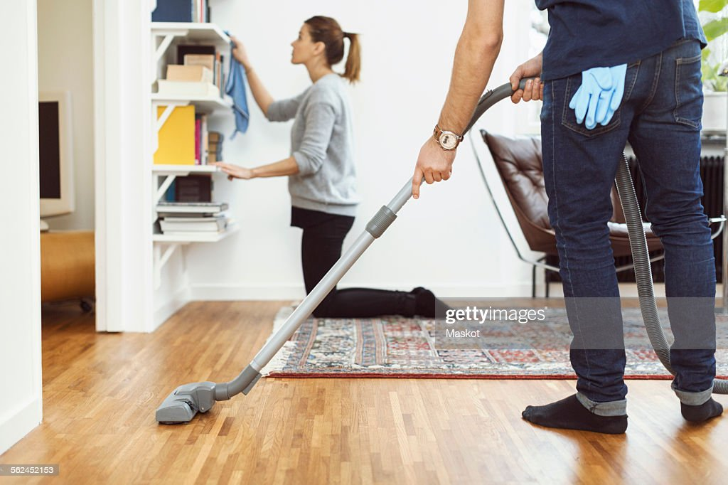 Low section of man vacuuming floor while woman cleaning shelves in background at home : Stock Photo