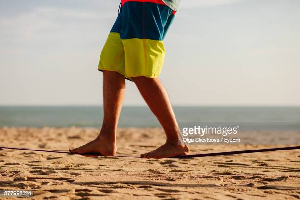 Low Section Of Man Walking At Beach