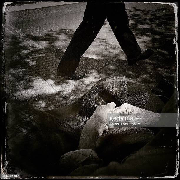 Low Section Of Man Walking By Homeless Person On Street