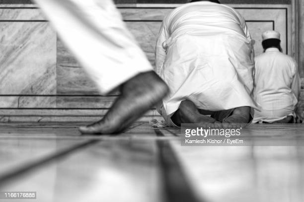 low section of man walking by people praying in mosque - foot worship stock pictures, royalty-free photos & images
