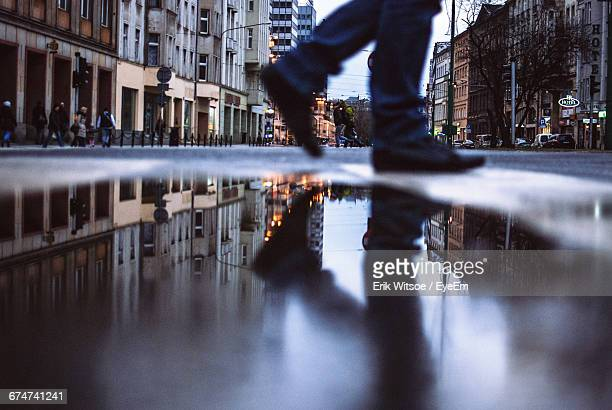 Low Section Of Man Walking By Puddle In City At Dusk