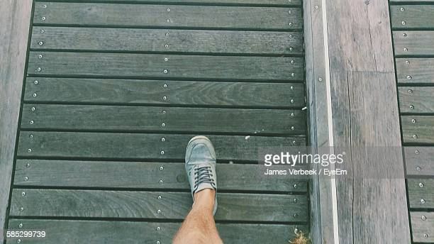 Low Section Of Man Walking On Boardwalk