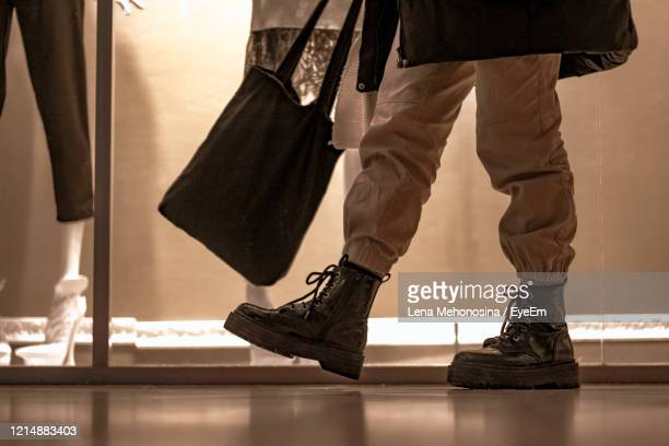 low section of man walking on floor at shopping mall - leather shoe stock pictures, royalty-free photos & images