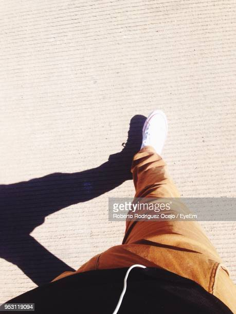 low section of man walking on footpath during sunny day - human leg stock photos and pictures