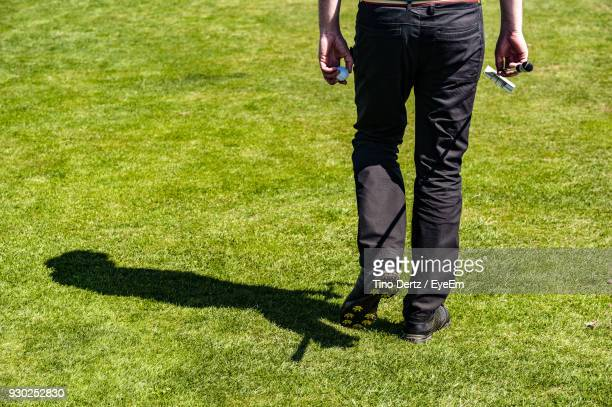 Low Section Of Man Walking On Golf Course