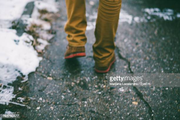 low section of man walking on ground during winter - marijana stock pictures, royalty-free photos & images