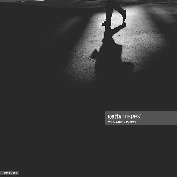 low section of man walking on pavement at night - low section stock pictures, royalty-free photos & images