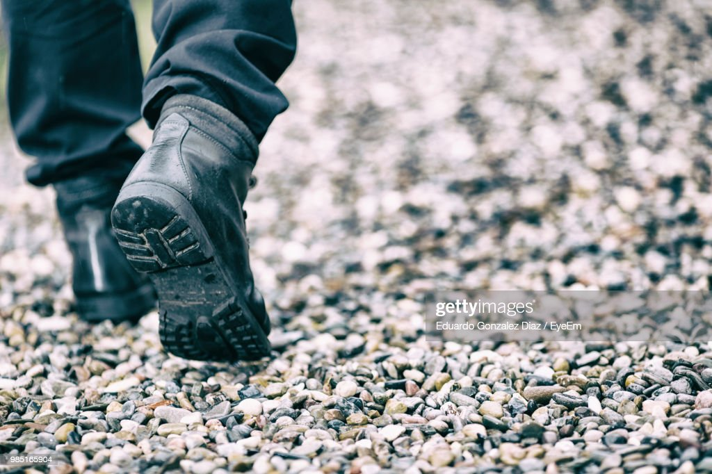 Low Section Of Man Walking On Pebbles : Stock Photo