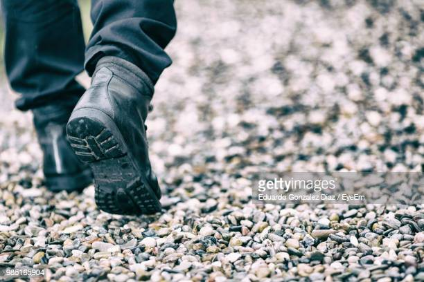 Low Section Of Man Walking On Pebbles