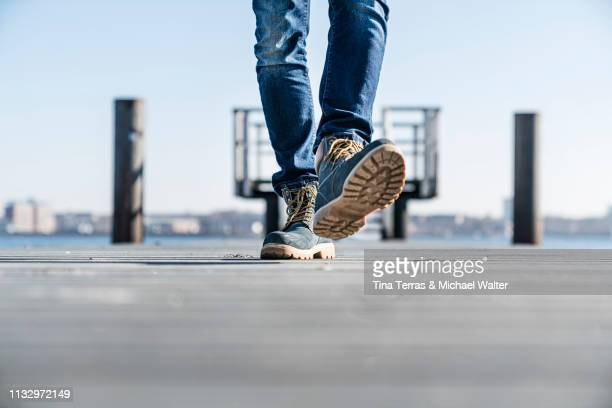 low section of man walking on pier on sunny day in germany. - sonnig imagens e fotografias de stock