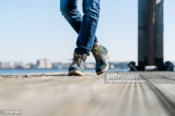 low section of man walking on pier on sunny day in germany. - vitalität stock pictures, royalty-free photos & images