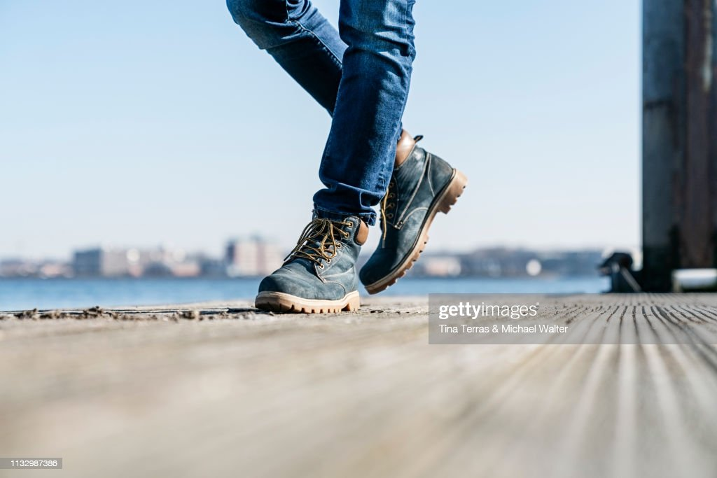 Low section of man walking on pier on sunny day in Germany. : Stock Photo