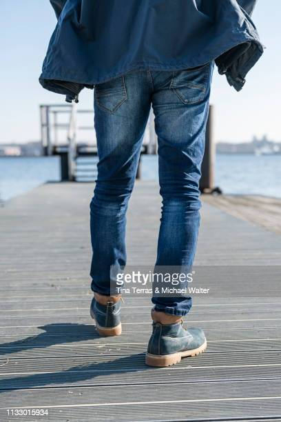 Low section of man walking on pier on sunny day in Germany.