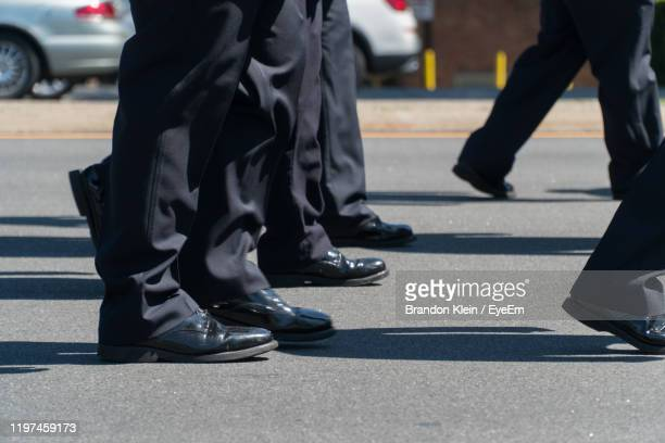 low section of man walking on road during event in city - klein stock pictures, royalty-free photos & images