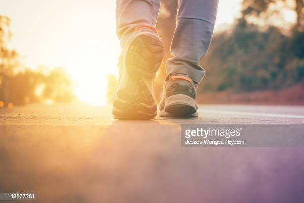 low section of man walking on road during sunset - foot stock pictures, royalty-free photos & images
