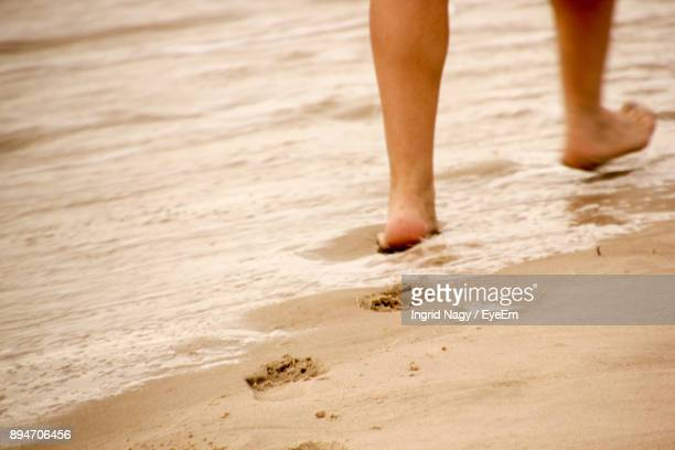 Low Section Of Man Walking On Sand At Beach