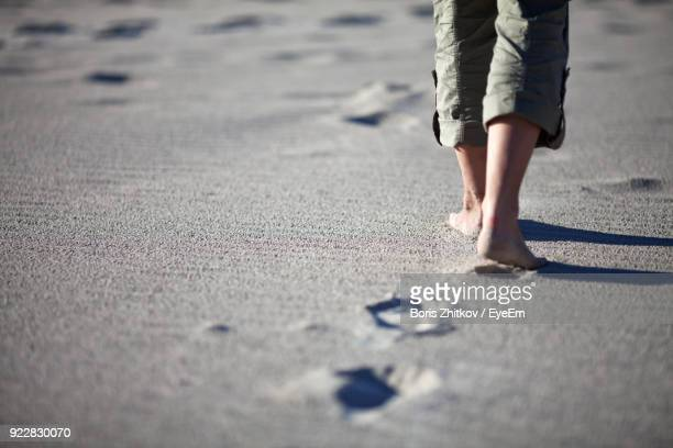 Low Section Of Man Walking On Sand