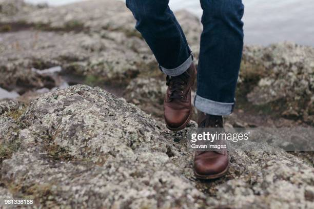 low section of man walking on shore - leather boot stock pictures, royalty-free photos & images
